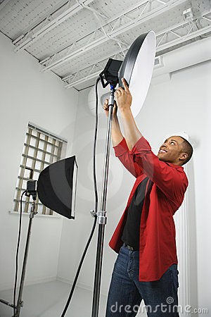 Young male adjusting studio lights.