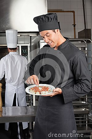 Chef Garnishing Dish In Kitchen