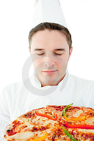 Young male cook smelling at pizza with closed eyes