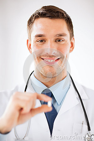 Young male doctor offering pill