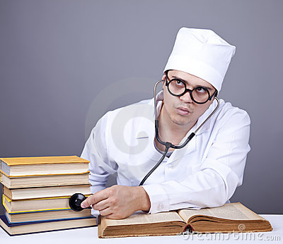Young male doctor studying medical books