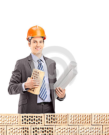 Young male engineer holding a brick and a blueprint behind brick