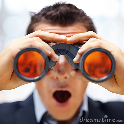 Young male entrepreneur looking through binoculars