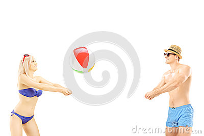 Young male and female in swimwear playing with a beach ball