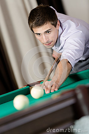 Male playing billiards at gambling club