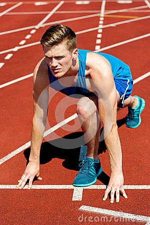 Young male sprinter in starting blocks