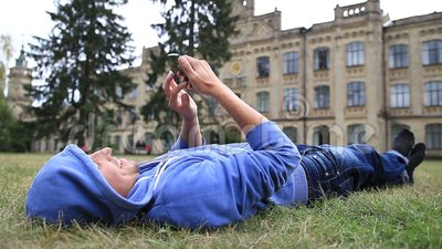 Young male student browsing on smart phone stock footage