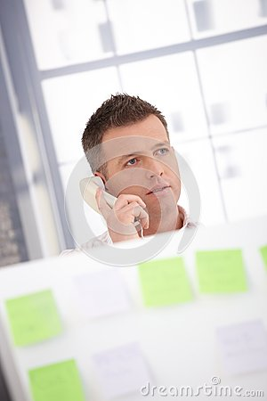 Young male talking on phone in office