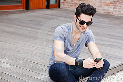 Young male texting on a smartphone
