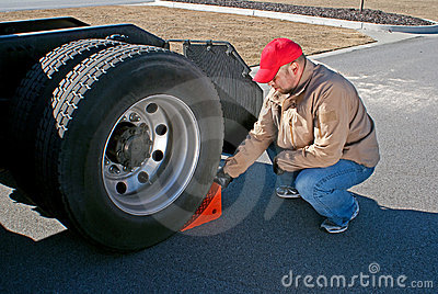 Young male truck driver chocking wheels for safety