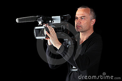 Young male videographer shooting at night