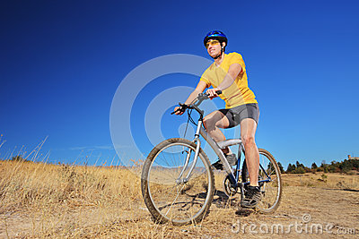 A young male with yellow shirt and helmet riding a bike outdoors