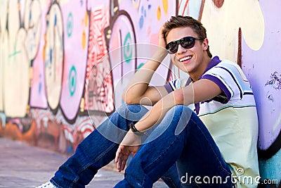 Young man against graffiti wall