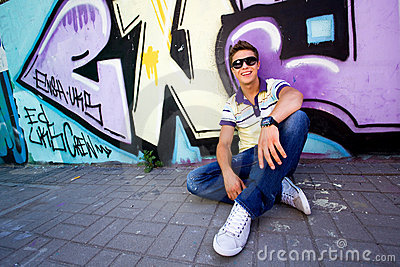Young man against graffiti wall