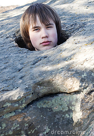 Young man in an aperture in  stone on  nature