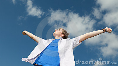 Young man with arms outstretched against sky