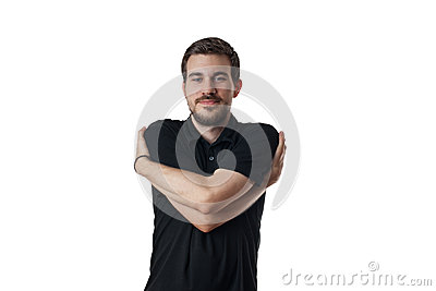 Young man with arms wrapped around himself