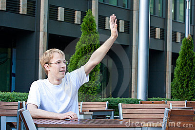 Young man is asking for waiter in cafe
