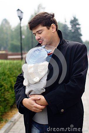 Young man with baby in a sling
