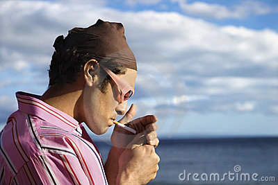 Young Man on Beach Lighting a Cigarette