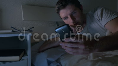 Young man in bed couch at home late at night using mobile phone in low light relaxed in communication technology stock footage
