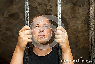 Young man behind the bars