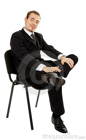 Young man in a black business suit sitting on a chair on a white ...