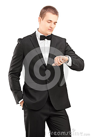 A young man in black suit with bow tie looking at wrist watch