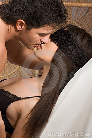 Young Man, blindfolded woman in love are kissing