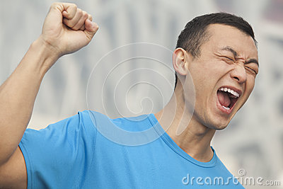 Young man in blue T-shirt with fist raised in the air, Beijing