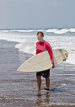 Young man with a board for surf on an ocean coast