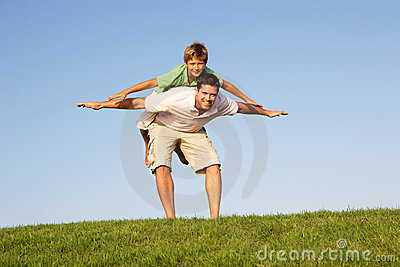 Young man with boy playing in a field