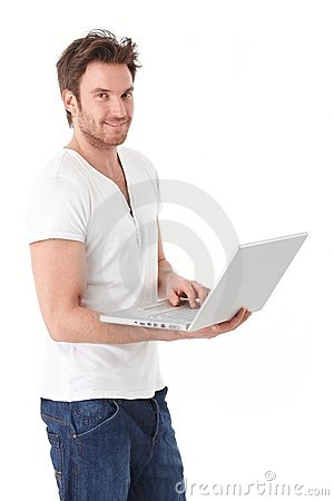 Young man browsing internet on laptop smiling Stock Photo