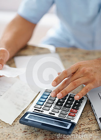 young man calculating bills at home