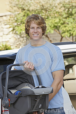 Young Man Carrying Cradle Standing By Car