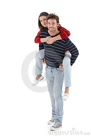 Young man carrying woman pickaback smiling