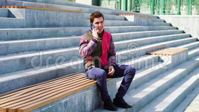 Young man talking on mobile phone in urban environment. Young man in casual wear sitting on wooden bench in urban environment and talking on mobile phone stock video footage
