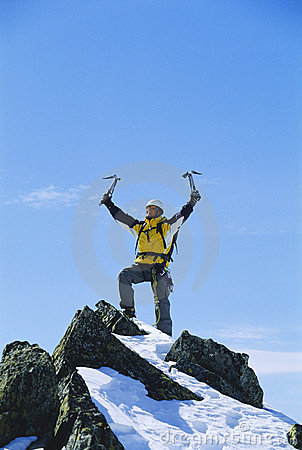 Young man celebrating reaching the top of mountain