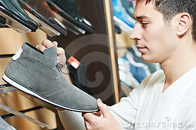Young man choosing shoe in clothes