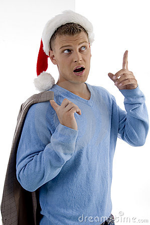 Young man with christmas hat pointing up