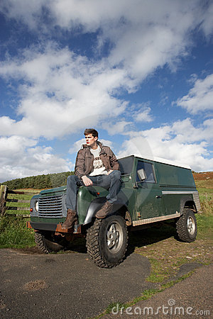 Young man in countryside with SUV