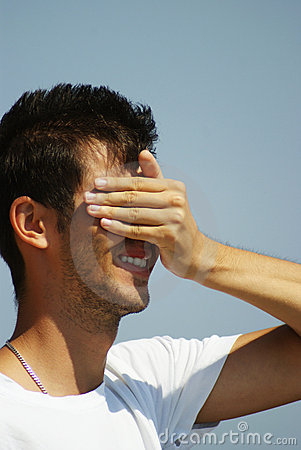 Young man covering his face