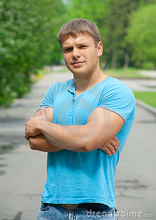Young man with crossed arms outdoors