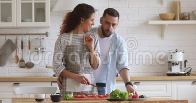 Young man cuddling smiling attractive wife in apron preparing food. Young handsome man cuddling from back smiling attractive wife in apron preparing healthy stock video