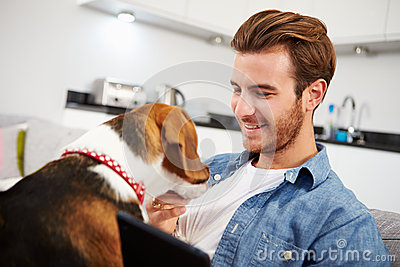 Young Man With Dog Sit On Sofa Using Digital Tablet