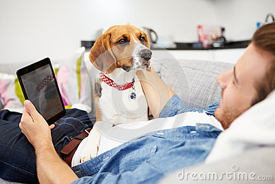 Young Man With Dog Sitting On Sofa Using Digital Tablet