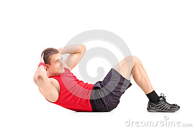 Young man doing abbs on the floor