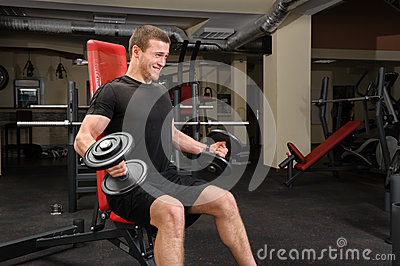Young man doing Dumbbell Biceps workout in gym