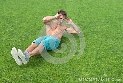 Young man doing sit-ups on green grass