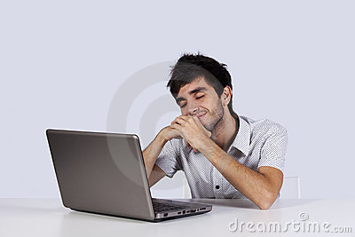 Young man dreaming in front of his laptop